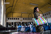 People are waiting for passenger trains inside the train station in Ayuttaya, Thailand.