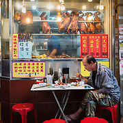 Man eating outside a restaurant in Kowloon, Hong Kong