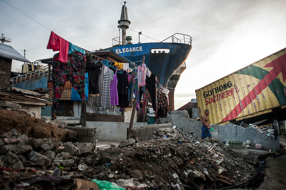 A man walks through debris and a beached boat in the streets of Tacloban on June 11 2014 in Tacloban, Philippines. Tacloban island was devastated after typhoon Hayan passed over leaving 6000 people dead and a high number of disappeared on November 2013.