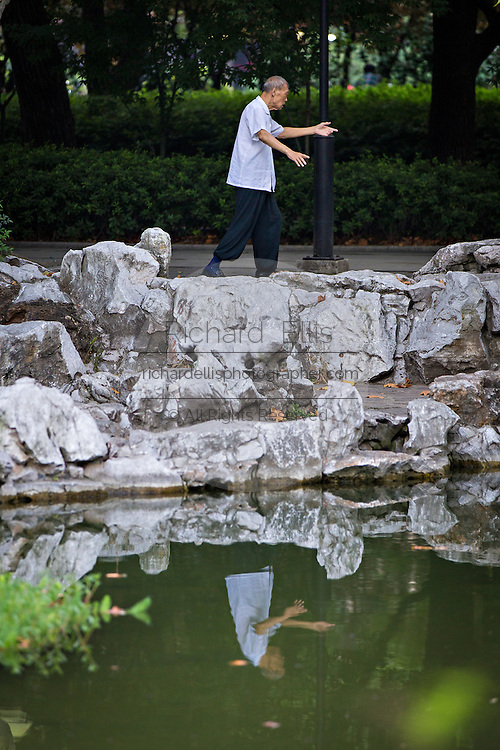 An elderly woman exercises in Fuxing Park Shanghai, China