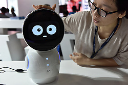 A woman demonstrates an inteligent robot which is made for children aged from 3 to 6 during the 4th China Information Technology Expo in Shenzhen, south China's Guangdong Province, April 8, 2016. The expo, with the participation of over 1,700 enterprises across the world, opened here Friday. EXPA Pictures © 2016, PhotoCredit: EXPA/ Photoshot/ Liang Xu<br /> <br /> *****ATTENTION - for AUT, SLO, CRO, SRB, BIH, MAZ, SUI only*****