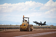 An F-22 lands nearby as construction crews are at work building new runways at Holloman Air Force Base in Otero County..HAFB received over $21 million to upgrade various facilities as part of the Recovery and Reinvestment Act.