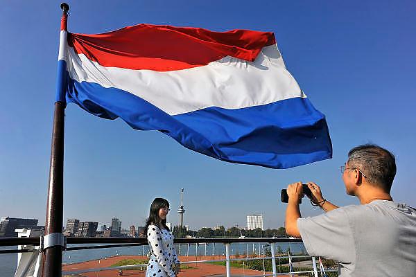 Nederland, Rotterdam,2-10-2011Toeristen uit China doen een toeristisch dagje wereldhaven. Zij komen uit HongKong. Vanaf de SS Rotterdam maakt een man een foto van een vrouw richting haven en euromast. De nederlandse vlag wappert uitbundig.Foto: Flip Franssen/Hollandse Hoogte