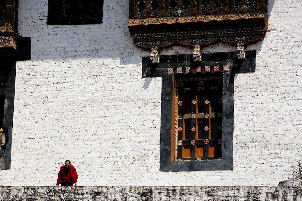 A monk looks over the wall at Trongsa dzong, Trongsa...Commonly described as the last Himalayan Shangrila, Bhutan is a country of unique serenity, harmony, and beauty. Nestled between India, China, and Tibet, this independent country whose name translates as 'the Land of the Thunder Dragon' has for the past 300 years  proactively followed a policy of isolation and cultural protection. Travel in and out of the country is strictly regulated, and the impact of outside influences on the local culture is carefully monitored. Spirituality is an important aspect of Bhutanese culture, with Buddhism being interlinked with everyday life. Gross National Happiness (GNH), as opposed to GNP/GDP, forms the cornerstone of its development strategy which focuses on a holistic development strategy that complements its cultural and Buddhist spiritual values.