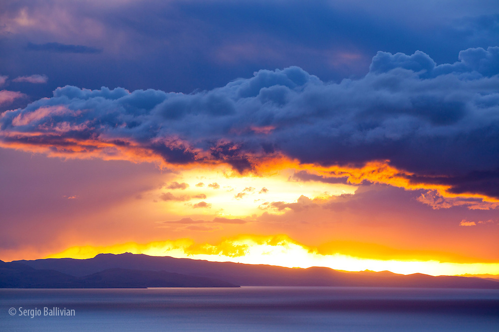 The Bolivian side of Lake Titicaca provides stunning backdrops to the setting sun after a rainstorm in the Andes.