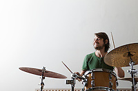 Young man plays drums with enjoyment