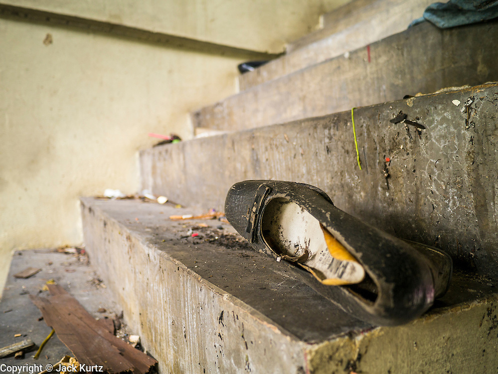16 OCTOBER 2012 - BANGKOK, THAILAND:  A woman's shoe on the stairs in an abandoned building on Phetchaburi Rd in central Bangkok, Thailand. The building used to be an optician's shop with residences above the ground floor shop. The global economic slowdown had little visible effect in Bangkok. Construction projects dot the city of 12 million and development continues unabated.   PHOTO BY JACK KURTZ