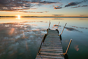 Dock at sunset reflecting in Lake Mitchell, at Lakeside Charlies restaurant, near Sun-N-Snow Motel, Cadillac, Michigan, USA.