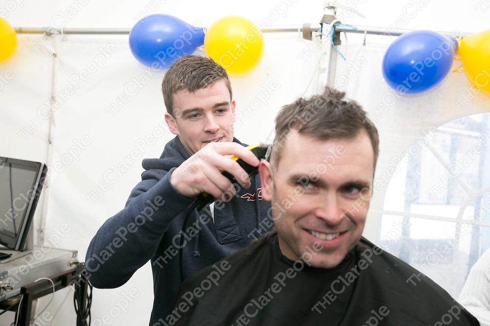 Clare Hurler Tony Kelly shaving Garda Frank Browne Heads  at  the Garda Shave or Dye event in O'Connell Square Ennis. .<br /> Pictured Credit Brian Gavin Press 22
