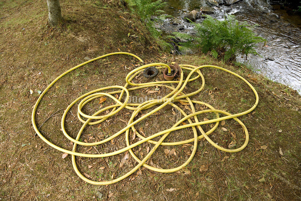 garden water hose near a little stream