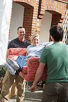 Two men outside house carrying woman on sofa