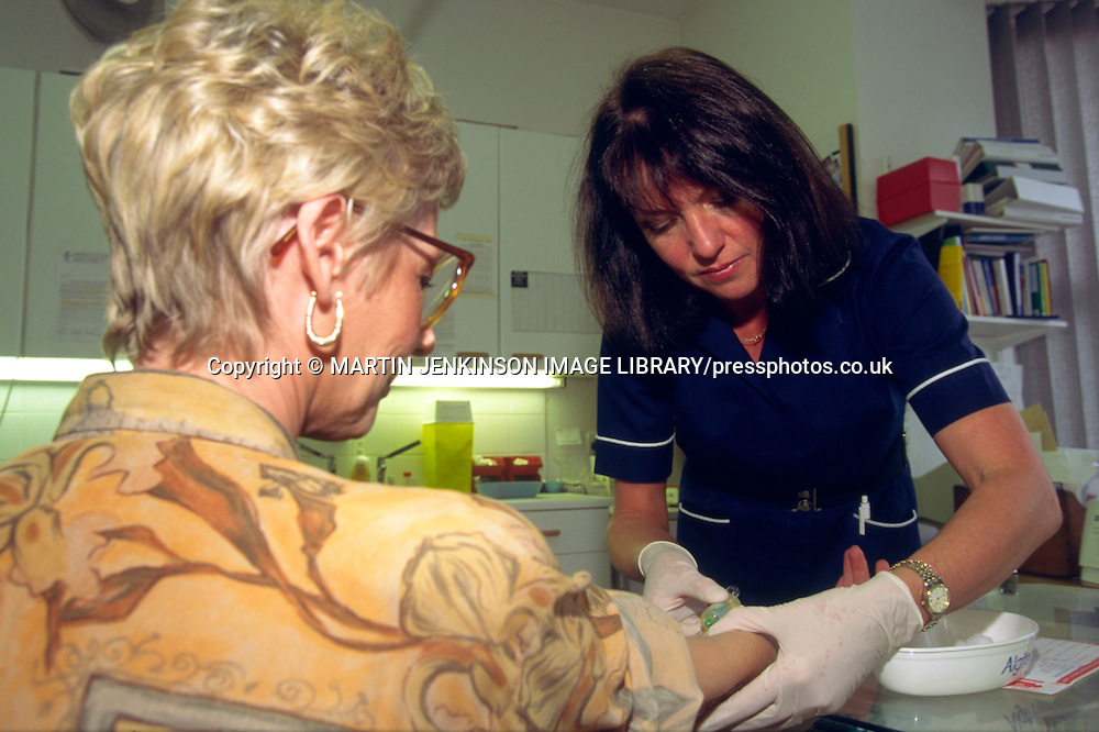 NHS Practice Nurse wearing gloves whilst taking a blood sample from a patient in a Doctors Surgery ....
