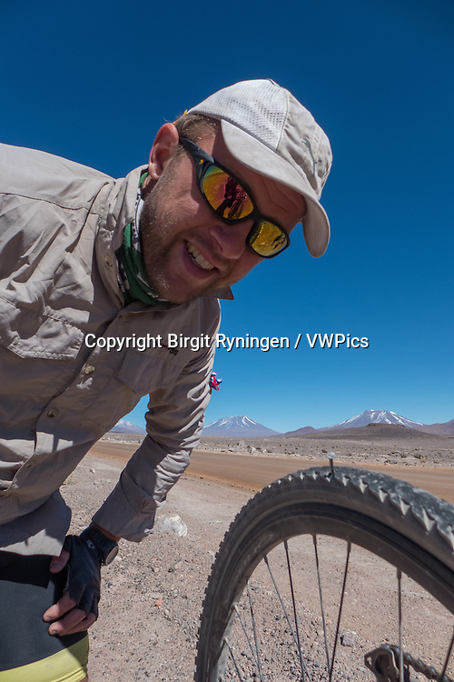 Cyclist having a flat, big time! Atacama, Chile