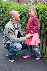 Father talking to his young daughter in the street,