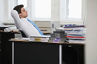 Business man relaxing at desk in office