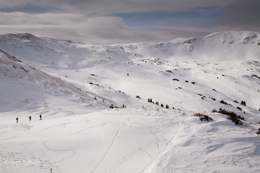 Skiers head down into the  backcountry bowls at Loveland Pass, Colorado.