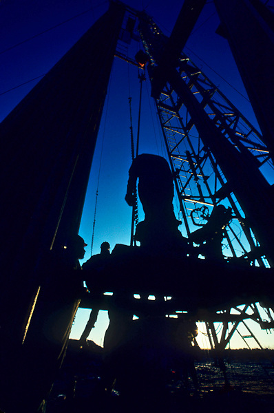 Silhouetted workers standing at the base of an on-shore oil drilling rig derrick at dusk.