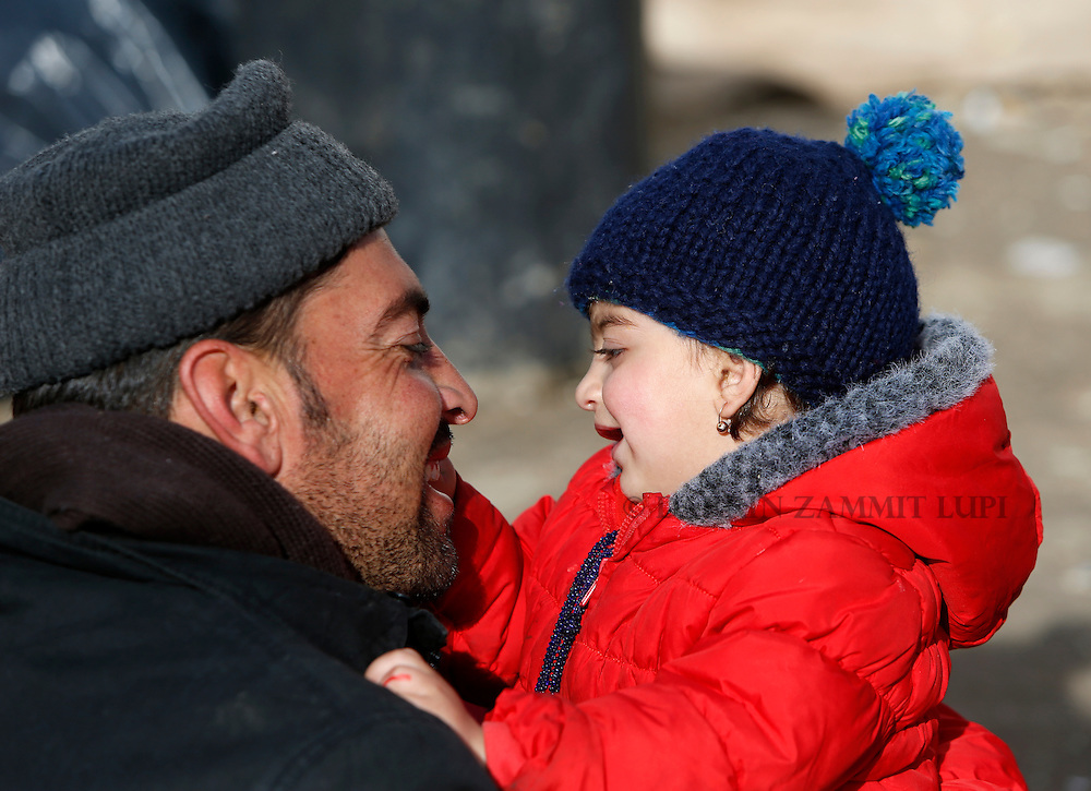 A migrant plays with a child as refugees and migrants wait to continue their journey towards western Europe from the Macedonia-Serbia border at a transit camp in the village of Presevo, Serbia, February 2, 2016.<br /> Photo: Darrin Zammit Lupi