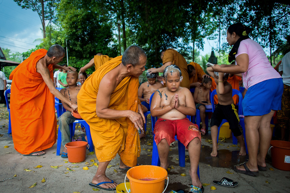 Each summer in rural Thailand, young men become novice Buddhist monks and spend several weeks learning Buddhist traditions with the guidance of older, experienced, monks. Here young men have their heads shaved as they prepare to for ordination into the Sangha in rural Nakhon Nayok, Thailand.