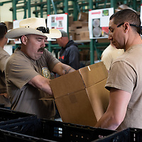 Todd Stevenson, left, and Michael Arocha, right, from the Naval Mobile Construction Battalion 18 help at the Community Pantry by filling food boxes on April 22, 2019 in Gallup.