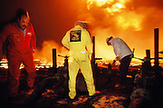 In March, 1991, heads of the three Texas oil well fire fighting companies made their first trip to Kuwait to survey the damage of the burning oil fields set ablaze by retreating Iraqi troops in February. Here in the Al Burgan field in mid afternoon, it was as dark as a moonless night due to the heavy thick smoke. The only light came from the more than 300 flaming oil wells and the truck headlights. It was raining soot and unburned oil. It was estimated that 5 or 6 million barrels of oil were being lost every day in this field alone. Huge oil lakes were forming. The men in the photo are: Boots Hansen (white jacket, Boots and Coots), Raymond Henry (Red Adair Company, red coveralls), Joe Bowden (Wildwell Control, yellow coveralls), and Larry Flak (oil well fire coordinator, black jacket).