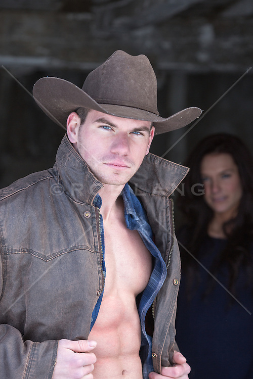 cowboy with an open shirt and a girl looking at him from behind