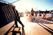 Two men skateboardng behind a mesh fence. Kristiansands Norway 2000