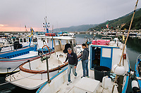 """PISCIOTTA, ITALY - 21 APRIL 2018: (L-R) Fishermen Vittorio Rimbaldo (56) and his son Marco (26) prepare their fishing boat before going out fishing alici di Menaica (Menaica anchovies) in Pisciotta, Italy, on April 21st 2018.<br /> <br /> Former restaurant owners Donatella Marino and her husband Vittorio Rimbaldo have spent the recent years preparing and selling salted anchovies, called alici di menaica, to a growing market thanks to a boost in visibility from the non-profit Slow Food.  The ancient Menaica technique is named after the nets they use brought by the Greeks wherever they settled in the Mediterranean. Their process epitomizes the concept of slow food, and involves a nightly excursion with the special, loose nets that are built to catch only the larger swimmers. The fresh, red anchovies are immediately cleaned and brined seaside, then placed in terracotta pots in between layers of salt, to rest for three months before they're aged to perfection.While modern law requires them to use PVC containers for preserving, the government recently granted them permission to use up to 10 chestnut wood barrels for salting in the traditional manner. The barrels are """"washed"""" in the sea for 2-3 days before they're packed with anchovies and sea salt and set aside to cure for 90 days. The alici are then sold in round terracotta containers, evoking the traditional vessels that families once used to preserve their personal supply.<br /> <br /> Unlike conventional nets with holes of about one centimeter, the menaica, with holes of about one and half centimeters, lets smaller anchovies easily swim through. The point may be to concentrate on bigger specimens, but the net also prevents overfishing. (26) prepare their fishing boat before going out fishing alici di Menaica (Menaica anchovies) in Pisciotta, Italy, on April 21st 2018.<br /> <br /> Former restaurant owners Donatella Marino and her husband Vittorio Rimbaldo have spent the recent years preparing and selling salted ancho"""