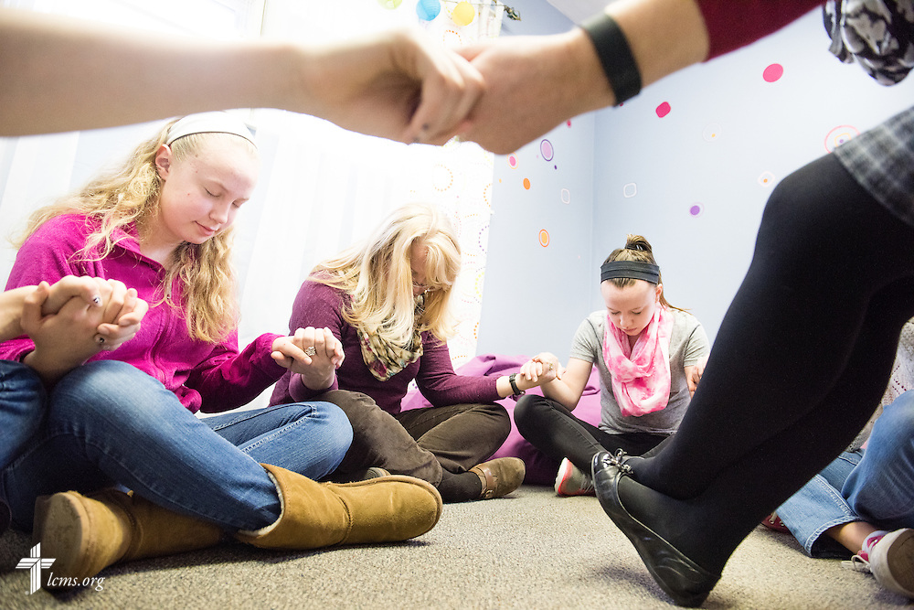 A group of young women and group leaders hold hands for prayer during a small group session following worship  at Brookfield Lutheran Church on Sunday, March 29, 2015, in Brookfield, Wis. Pictured (L-R) is Anna Gaskell, Cheryl Evans, and Katie Doherty.  LCMS Communications/Erik M. Lunsford
