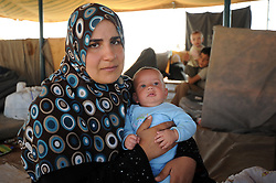 Syrian refugees at the Zaatari refugee camp in Jordan. New arrivals waiting to be given a tent. Um Ammar 34 years old with her 4 month baby, September 3, 2012. Photo by Nick Cornish/i-Images.