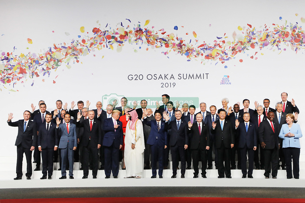 """CORRECTION - (Front L-R) Brazil President Jair Bolsonaro, French President Emmanuel Macron, Indonesia President Joko Widodo, Chinese President Xi Jinping, US President Donald Trump, Saudi Arabia's Crown Prince Salman, Japan Prime Minister Shinxo Abe, Argentine President Mauricio Macri, Russian President Vladimir Putin, Turkish President Recep Tayyip Erdogan, South Korean President Moon Jae-in, South African President Cyril Ramaphosa, Netherlands Prime Minister Mark Rutte, (Second row L-R) Spanish Prime Minister Pedro Sanchez, Egypt President Abdel Fattah el-Sisi, President of the European Commission Jean-Claude Juncker, Australia's Prime Minister Scott Morrison, British Prime Minister Theresa May, India Prime Minister Narendra Modi, Canada Prime Minister Justin Trudeau, Italian Prime Minister Giuseppe Conte, European Union President of the European Council Donald Tusk, Senegal President Macky Sall, Chile President Sebastian Pinera and Singapore Prime Minister Lee Hsien Loong and third row's invited guests attend the family photo during the G20 Osaka Summit in Osaka on June 28, 2019. (Photo by Ludovic MARIN / AFP) / """"The erroneous mention[s] appearing in the metadata of this photo by Ludovic MARIN has been modified in AFP systems in the following manner: [Crown Prince] instead of [King]. Please immediately remove the erroneous mention[s] from all your online services and delete it (them) from your servers. If you have been authorized by AFP to distribute it (them) to third parties, please ensure that the same actions are carried out by them. Failure to promptly comply with these instructions will entail liability on your part for any continued or post notification usage. Therefore we thank you very much for all your attention and prompt action. We are sorry for the inconvenience this notification may cause and remain at your disposal for any further information you may require.î"""