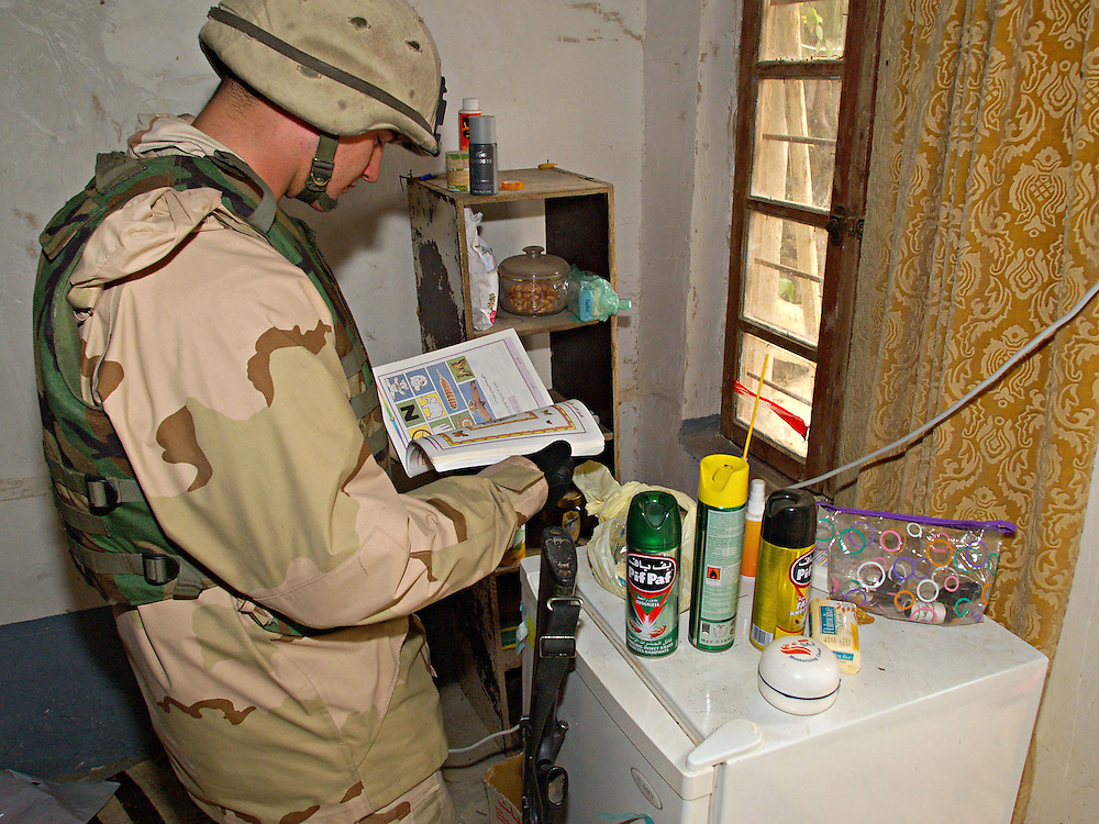 Dec15th 2003.ad Dawr, Iraq..Saddams hideout..A US soldier examines belonings left behind by the dictator Saddam who was captured at this farm house near Tikrit.
