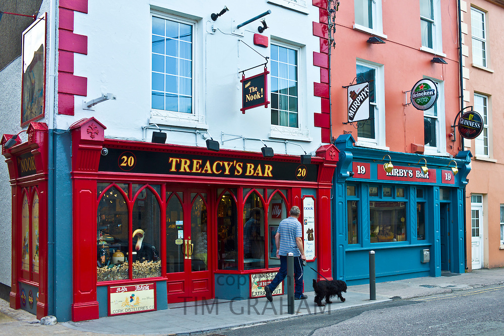 Man walking dog past Treacy's Bar and Kirby's Bar in Youghal, popular tourist town in County Cork, Ireland