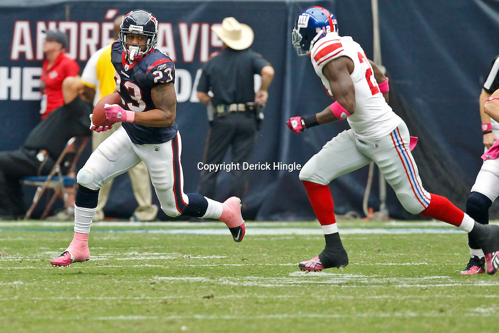 October 10, 2010; Houston, TX USA; Houston Texans running back Arian Foster (23) is pursued by New York Giants safety Kenny Phillips (21) during the second half at Reliant Stadium. The Giants defeated the Texans 34-10. Mandatory Credit: Derick E. Hingle