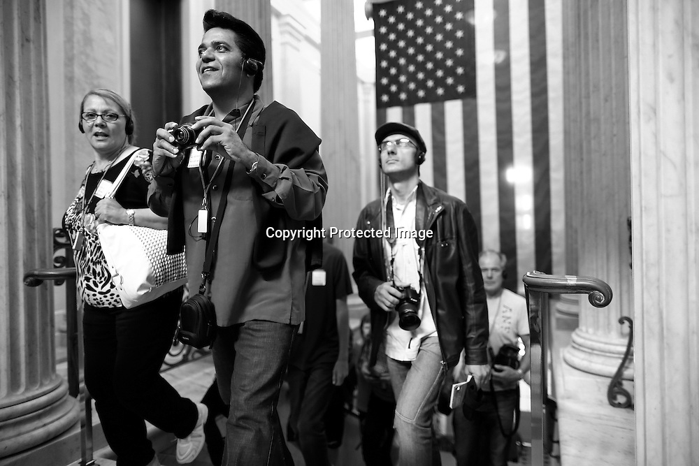 Tourists react as they enter the U.S. Capitol Rotunda on an official visitors' tour, which had been suspended during the 16-day government shutdown, at the U.S. Capitol in Washington, October 17, 2013. The U.S. Congress on Wednesday approved an 11th-hour deal to end a partial government shutdown and pull the world's biggest economy back from the brink of a historic debt default that could have threatened financial calamity.
