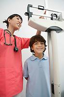 Female doctor weighting patient