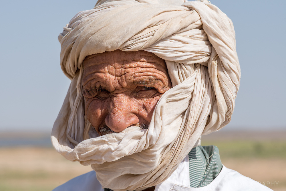 A berber shepherd in his tagelmust (the Moroccan turban also known as Cheche) stands for a portrait while flock grazes the grass growing along the banks of a pond.  Merzouga, Morocco.