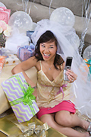 Bride photographing herself using mobile phone