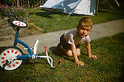 A young boy sits on the grass after falling from his tricycle on a summer's day in the family garden in the early nineteen sixties.