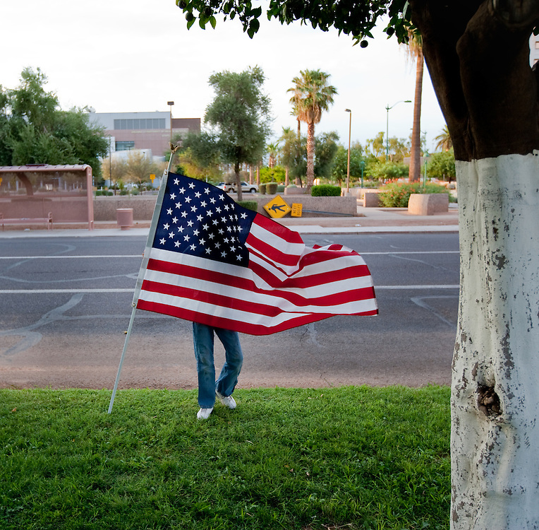 Dariana Yanez, age 10, waves the American Flag as she protests against SB1070 in front of the State Capitol in Phoenix.