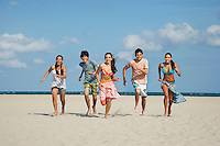 Group of teenagers (16-17) running on beach