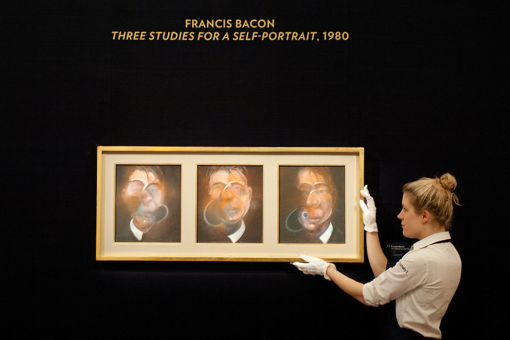 A Sotheby's employee poses in front of a painting entitled 'Three studies for a Self-Portrait) by Francis Bacon (Est £10-15 million) during the press preview of the Sotheby's forthcoming February sales of Impressionist & Modern Art and Contemporary Art in London, including works by Picasso, Bacon, Monet, Richter, Miró, Basquiat.