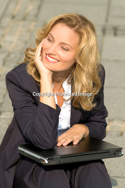 Young business woman smiling, with a laptop computer