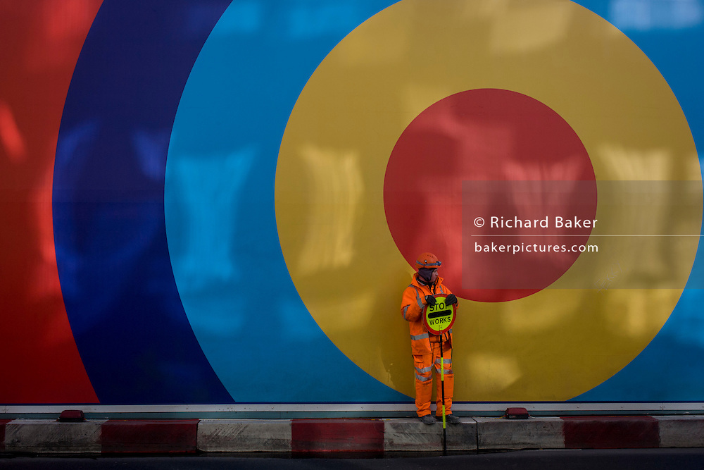 A banksman working on a nearby building site, holds his Stop sign under the large circles of a construction hoarding on central London's Oxford Street.