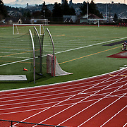 Ballard High School playfield and track with Mount Rainier and downtown skyscrapers seen in distance over Queen Anne Hill, Seattle, Washington