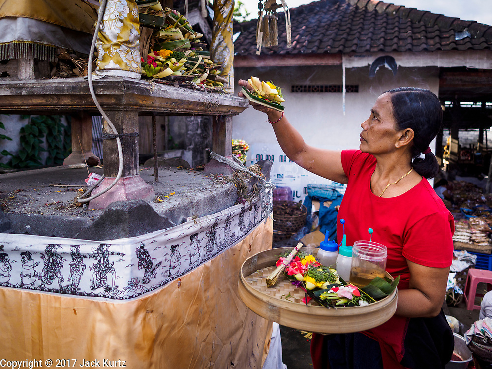 07 AUGUST 2017 - BEBANDEM, BALI, INDONESIA:  A woman makes an offering at the small temple in the market in Bebandem, in far eastern Bali. The market is known for baskets, which are woven in the area. Bali's local markets are open on an every three day rotating schedule because venders travel from town to town. Before modern refrigeration and convenience stores became common place on Bali, markets were thriving community gatherings. Fewer people shop at markets now as more and more consumers go to convenience stores and more families have refrigerators.    PHOTO BY JACK KURTZ