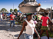 18 NOVEMBER 2010 - PORT-AU-PRINCE, HAITI: A woman carries her laundry to a stream running through a suburb of Port-au-Prince, Haiti, Thursday morning.  An outbreak of cholera in northern Haiti about a month ago has spread across the nation. Tens of thousands of people have been hospitalized and treated for cholera and more than 1,100 have died. Cholera is a water borne illness that causes severe diarrhea and death by dehydration in a matter of hours.   PHOTO BY JACK KURTZ  choleraepidemic