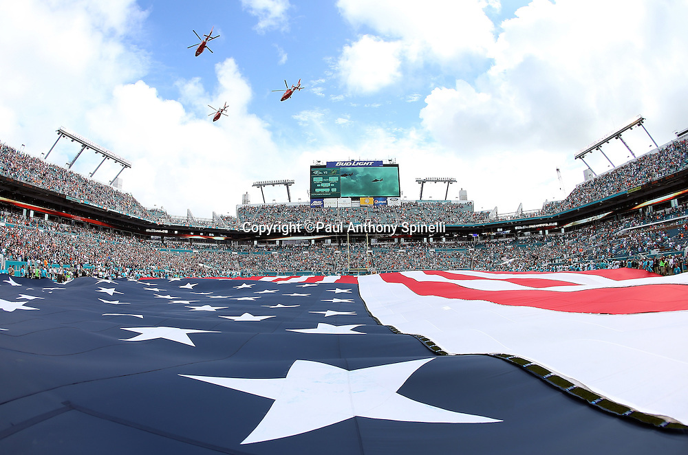 Helicopters fly over Sun Life Stadium while a giant American flag covers the field during the playing of the National Anthem in this general view photograph taken from field level before the Miami Dolphins 2015 week 13 regular season NFL football game against the Baltimore Ravens on Sunday, Dec. 6, 2015 in Miami Gardens, Fla. The Dolphins won the game 15-13. (©Paul Anthony Spinelli)