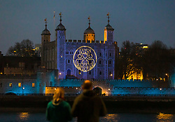 © Licensed to London News Pictures. 09/04/2020. London, UK. A couple stop briefly to look at light projections onto the Tower of London this evening in recognition and appreciation of National Health Service (NHS) and key workers during the ongoing COVID-19 coronavirus epidemic. Photo credit: Vickie Flores/LNP