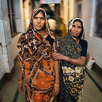 Shashi, age 25, and her mother-in-law Asarphi, head towards the labour ward of Shivpuri District Hospital. Shashi, from Chitora village, is pregnant with her second child. She had arrived at the hospital after traveling 12 km in the new ambulance service available throughout Shivpuri district. Shashi accessed the ambulance by calling the 24-hour phone line which is one means by which the government and partners UNICEF are increasing the rate of institutional deliveries in Madhya Pradesh state. ..Shivpuri district in Madhya Pradesh suffers from poor health outcomes. Of particular concern is the high rate of maternal mortality. One of the Indian government's aims, with partners Unicef, is to encourage the population to adopt practices to improve sanitation and health practices. In an area made up of traditionally disadvantage groups and suffering low literacy rates, this can be a challenge. ..A survey found that radio was the most readily accessible media by the Shivpuri community with more than half saying they tuned in several times a day. ..Dharkan 107.8 FM will go on air in July. The station that will broadcast to 75 villages in a 15-kilometer radius reaching 170,000 people...Rather than preaching educational messages, the station, which is already producing pilot programs, uses humor and folk artists performing in the local language to entertain and inform their audiences. There is a major impact, especially on women, who are contributing their voices to such wide-ranging issues as caste discrimination, female feticide and women,A?o?s empowerment. ..Photo: Tom Pietrasik.Shivpuri, Madhya Pradeh. India.June 2009